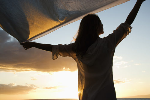 Attractive Caucasian mid-adult woman holding up fabric in breeze silhouetted by sunset beside ocean.