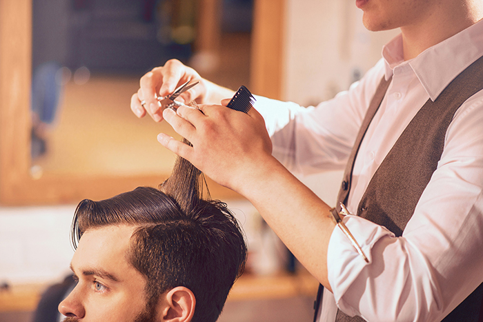 Know your craft. Pleasant handsome man sitting in the barbershop while professional skillful barber cutting his hair
