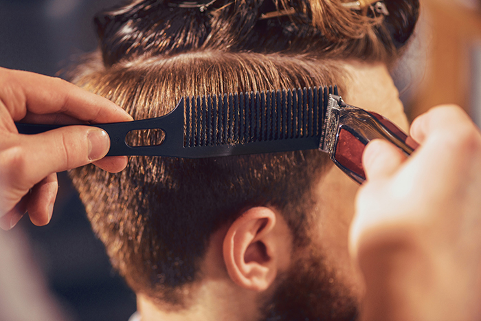 Make it short. Professional barber holding razor and cutting  hair of his client