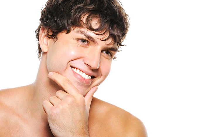 Portrait of handsome young man with clean-shaven face and happy smile